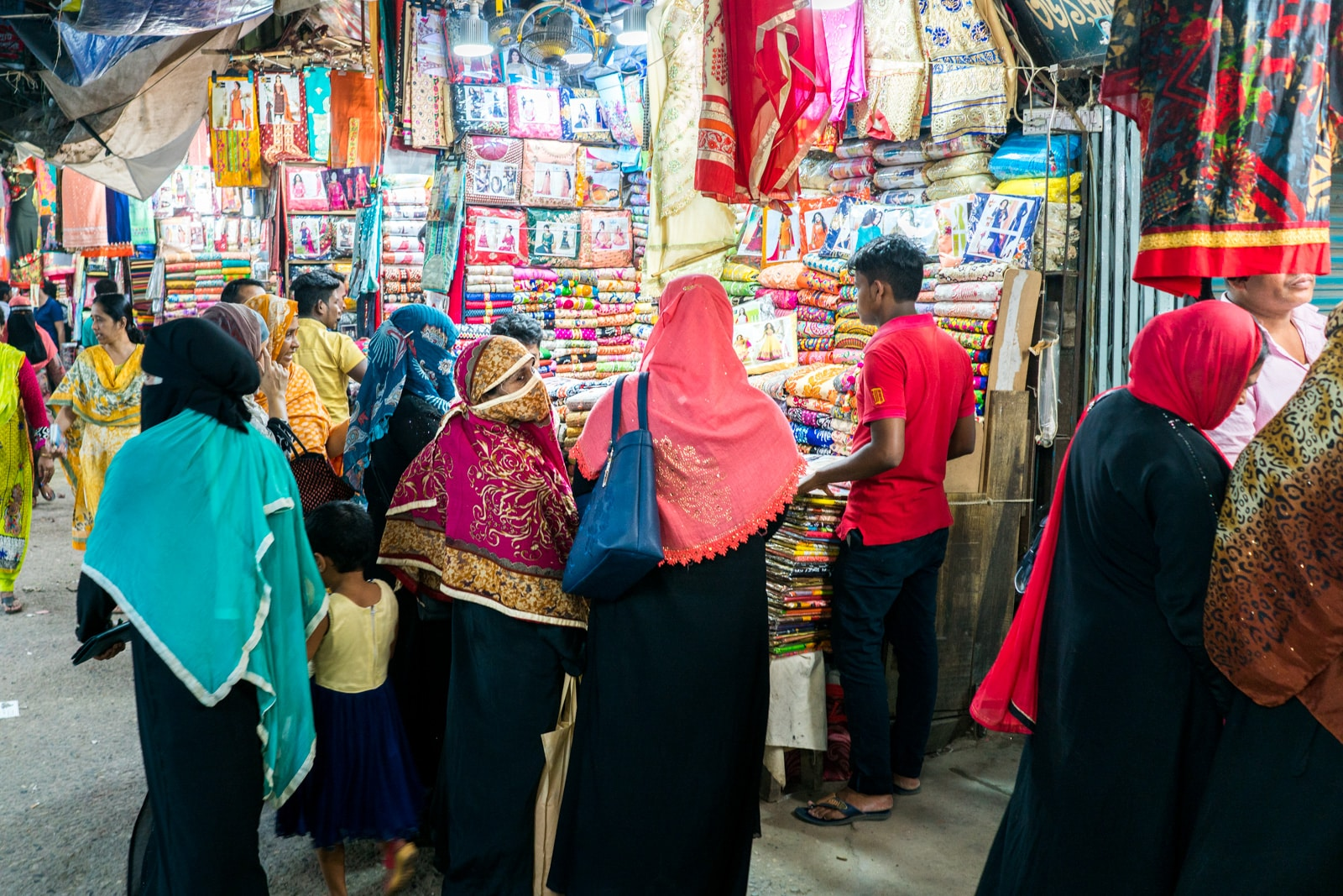 Traveling as a woman in Bangladesh - Women in black abayas with colorful headscarves shopping in the markets of Old Dhaka - Lost With Purpose travel blog