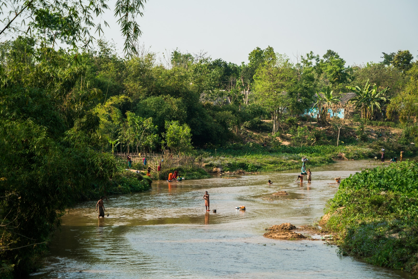 Backpacking in Bangladesh travel guide - people washing in a stream in Srimangal - Lost With Purpose travel blog