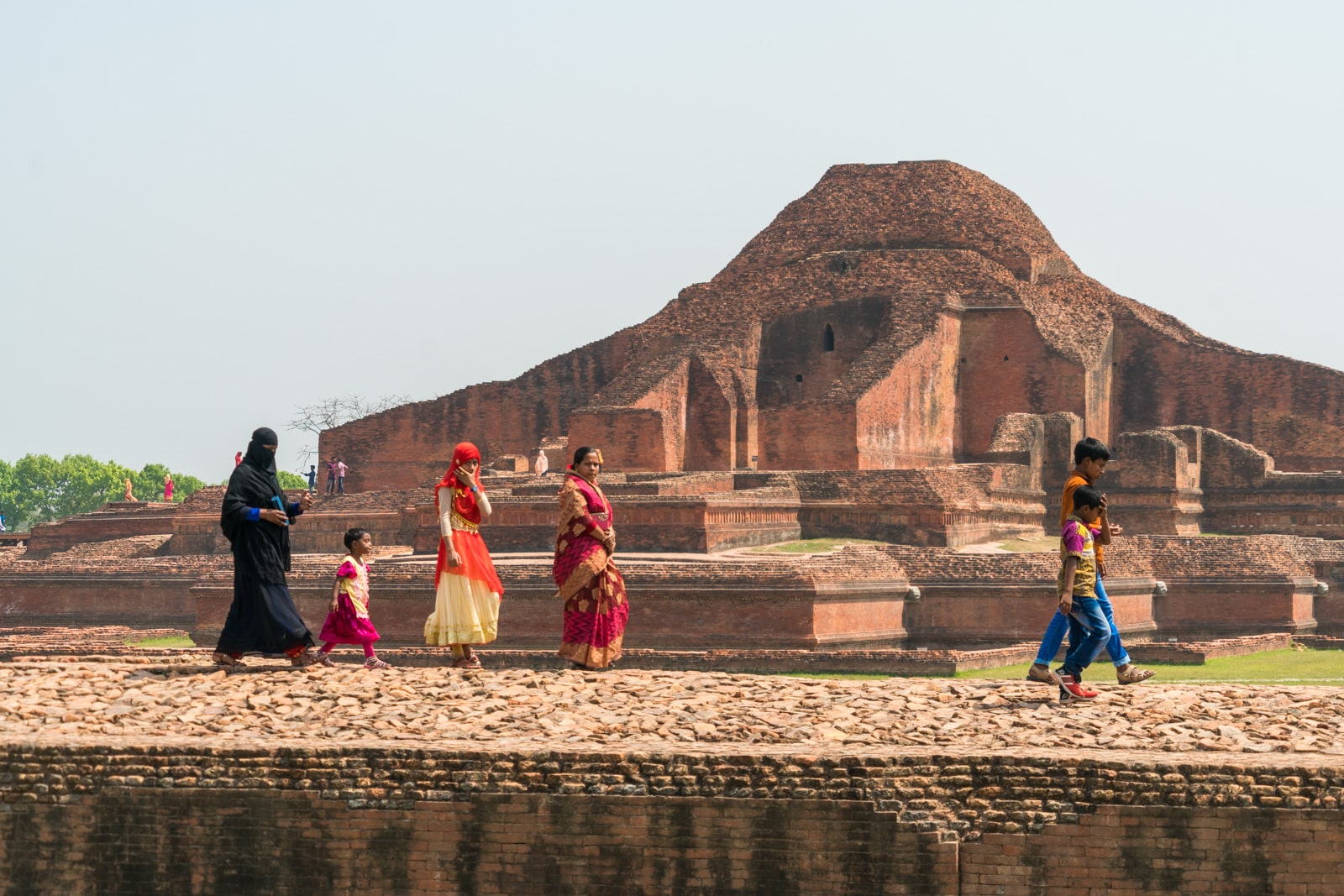 Backpacking in Bangladesh travel guide - Muslim family walking by Buddhist ruins of Sompur Mahavihara - Lost With Purpose travel blog