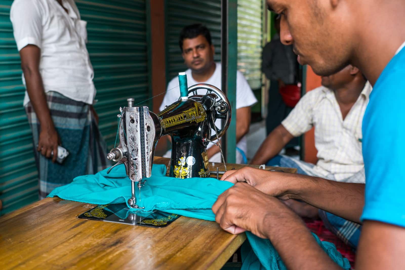 Easy ways to be a more responsible traveler - Tailor sewing up ripped pants - Lost With Purpose travel blog