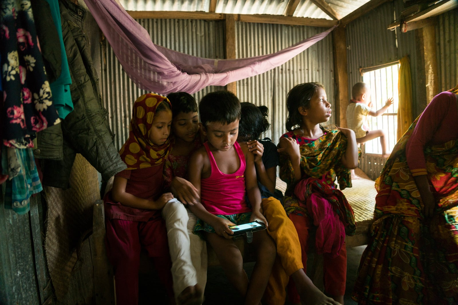 Travel guide to Nijhum Dwip, Bangladesh - Village children on a mobile phone - Lost With Purpose travel blog