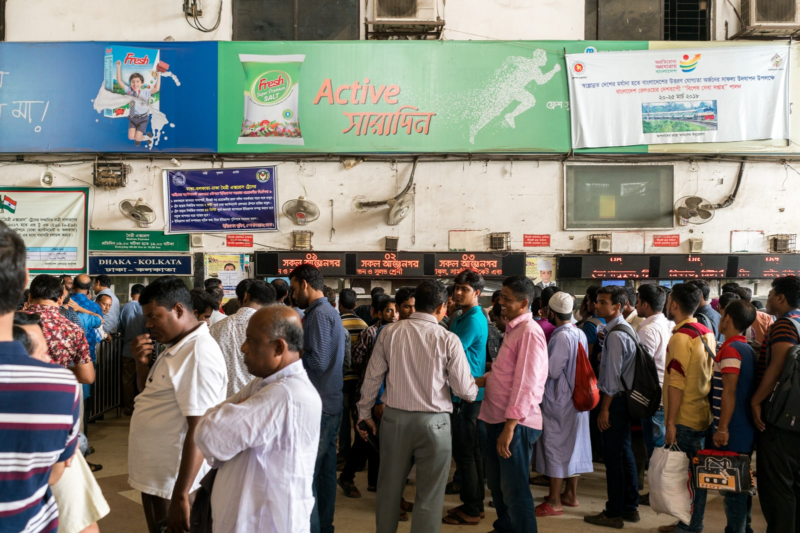 How to take the train from Bangladesh to India - Ticketing windows at Dhaka Kamalapur railway station - Lost With Purpose travel blog