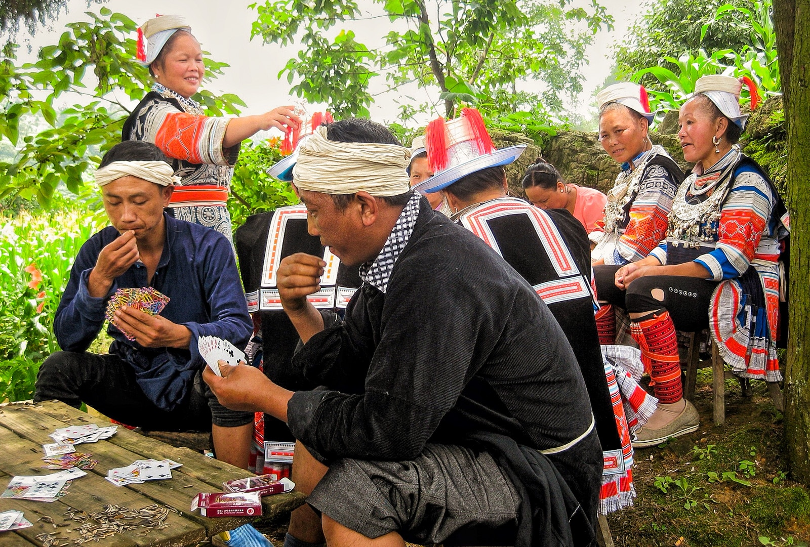Exploring off the beaten track villages in Guizhou, China - Geija locals in traditional dress eating sunflower seeds