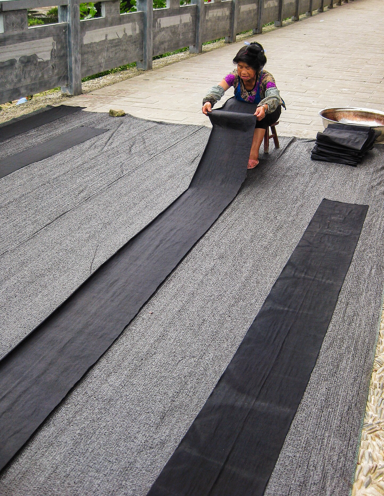 Exploring off the beaten track villages in Guizhou, China - Woman drying indigo dyed material in Zhouxi