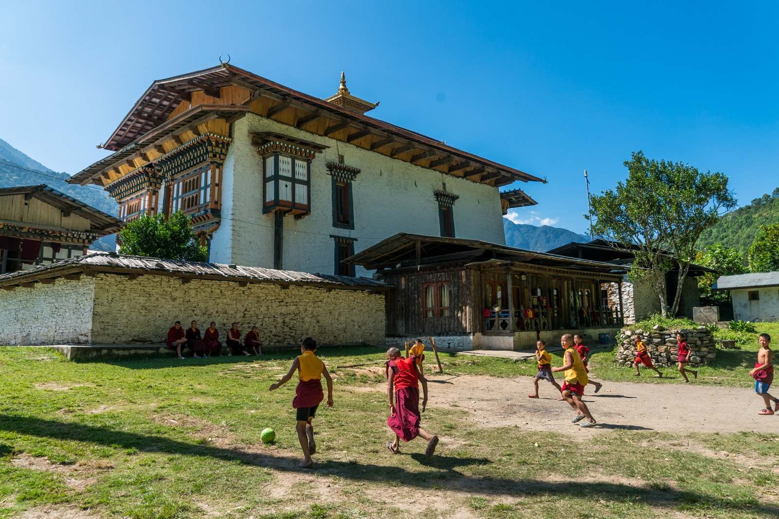 Stunning photos of Bhutan - Young monks playing football outside Inndocholing dzong - Lost With Purpose travel blog