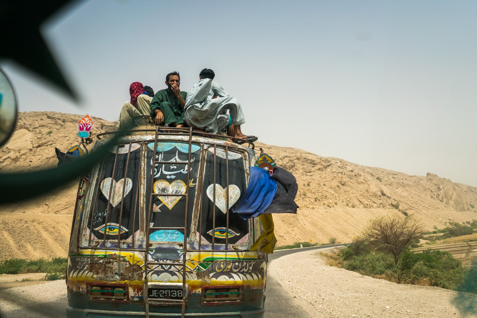 The Urs of Lal Shahbaz Qalandar in Sehwan, Pakistan - Men riding on top of a bus - Lost With Purpose travel blog