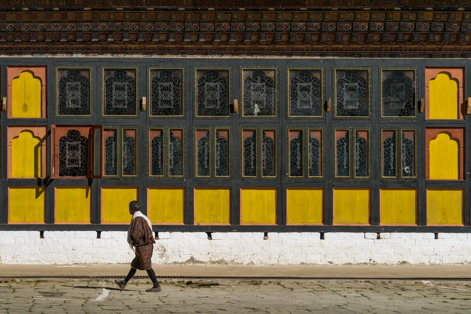 Stunning photos of Bhutan - Man walking in traditional gho in Gangtey Monastery - Lost With Purpose travel blog