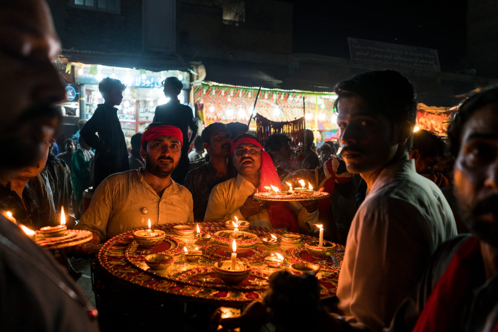 The Urs of Lal Shahbaz Qalandar in Sehwan, Pakistan - Men with candles on the streets at night - Lost With Purpose travel blog
