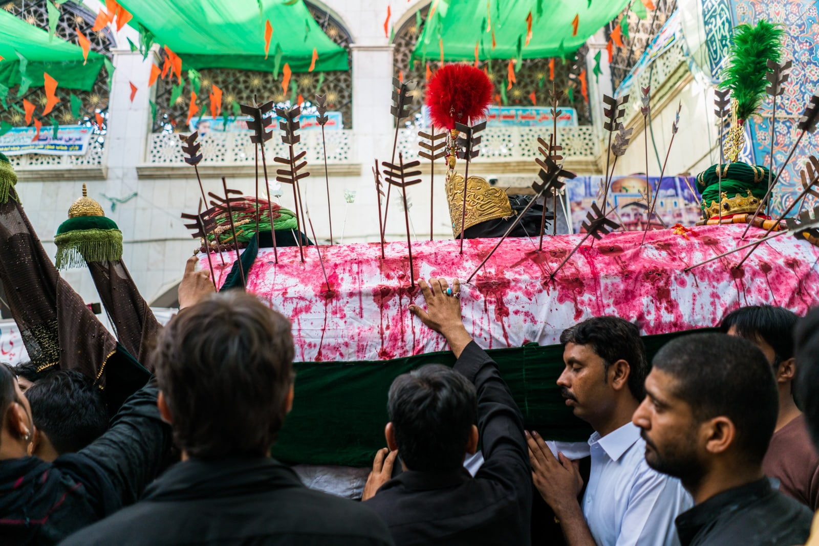 The Urs of Lal Shahbaz Qalandar in Sehwan, Pakistan - Man touching Shia coffin with blood and arrows outside the shrine - Lost With Purpose travel blog