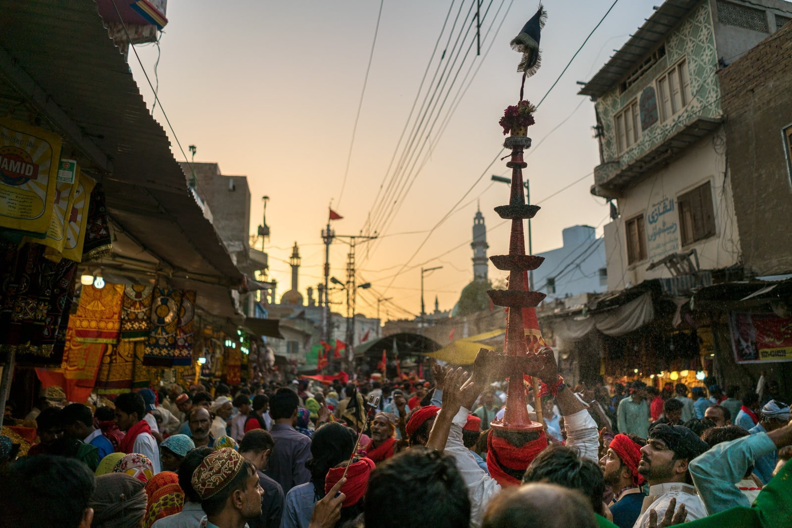 The Urs of Lal Shahbaz Qalandar in Sehwan, Pakistan - Busy streets and man carrying tower - Lost With Purpose travel blog