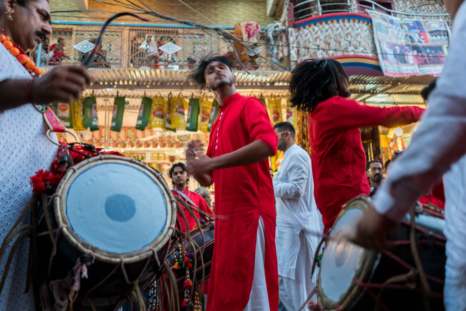 The Urs of Lal Shahbaz Qalandar in Sehwan, Pakistan - Boy in red dancing to drums outside the shrine - Lost With Purpose travel blog