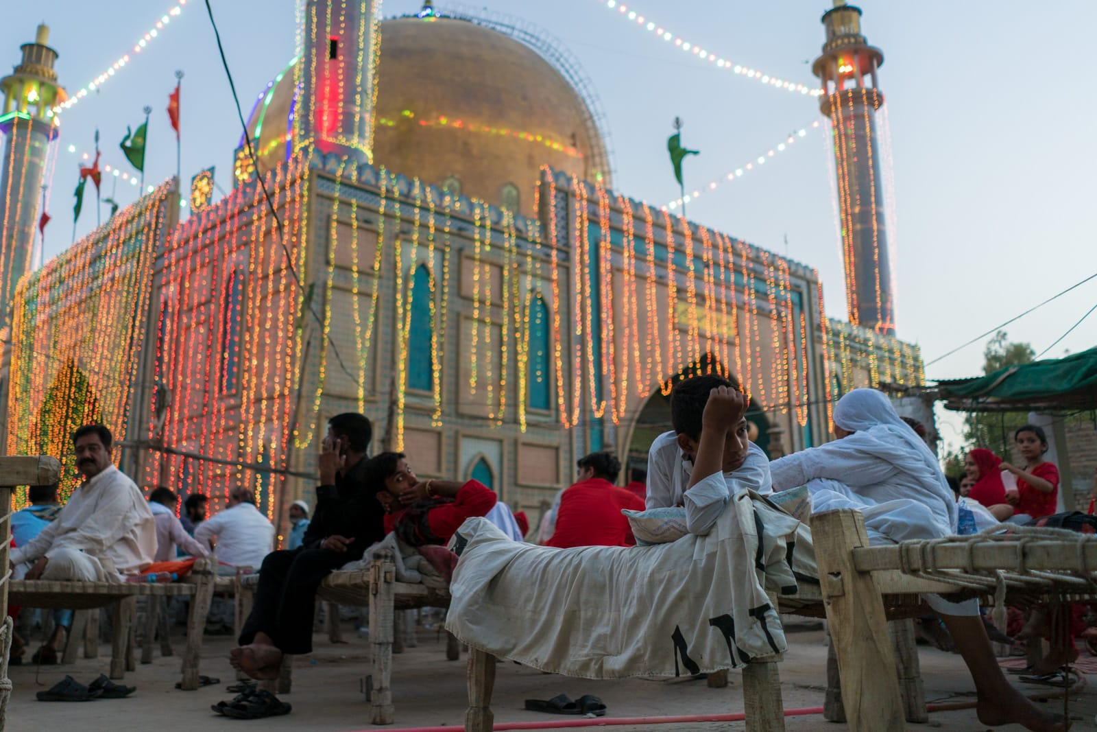 The Urs of Lal Shahbaz Qalandar in Sehwan, Pakistan - Boy lounging on charpoy bed near shrine - Lost With Purpose travel blog