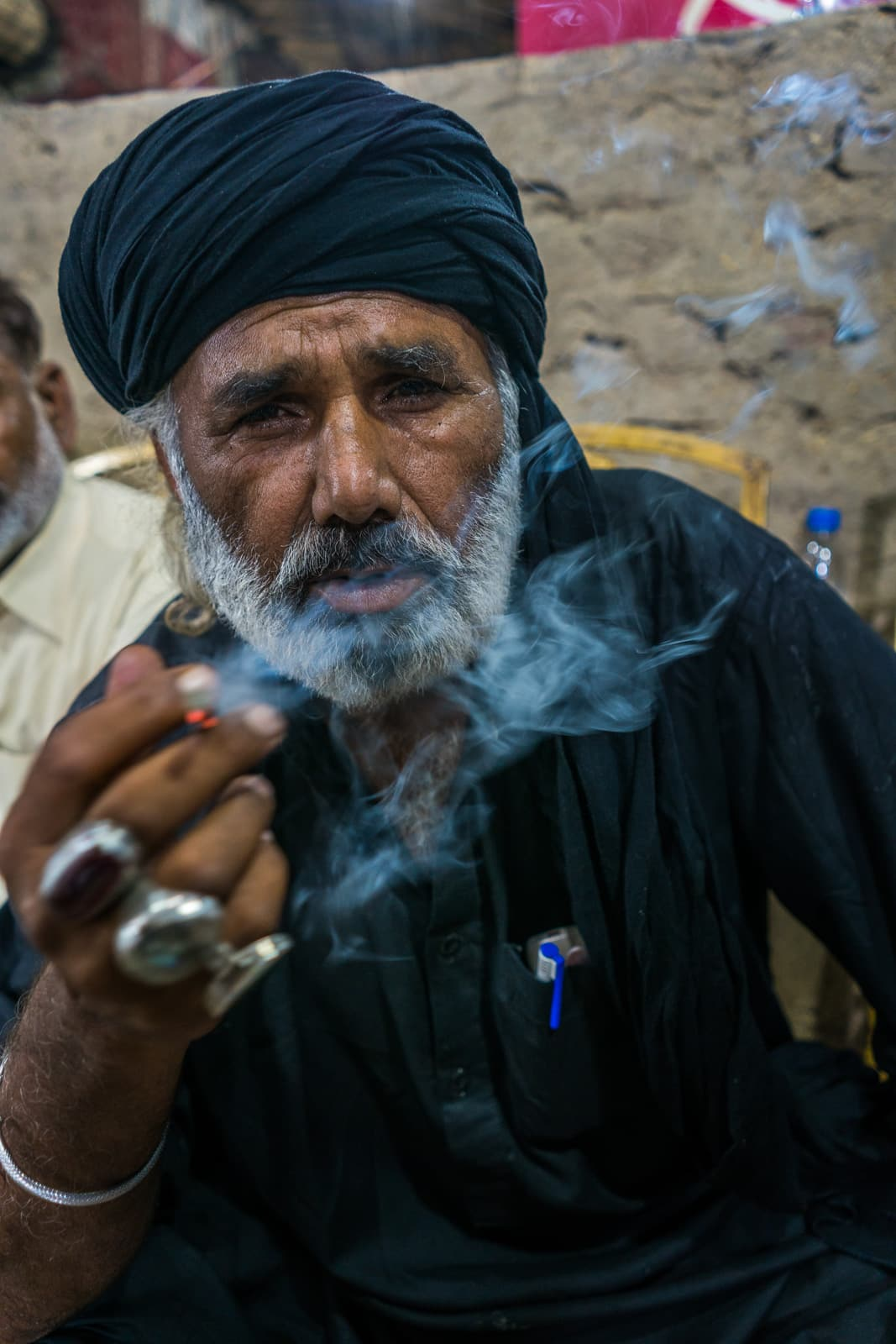 A Sufi melang in black smoking a cigarette at the Urs of Lal Shahbaz Qalandar in Sehwan Sharif, Pakistan.