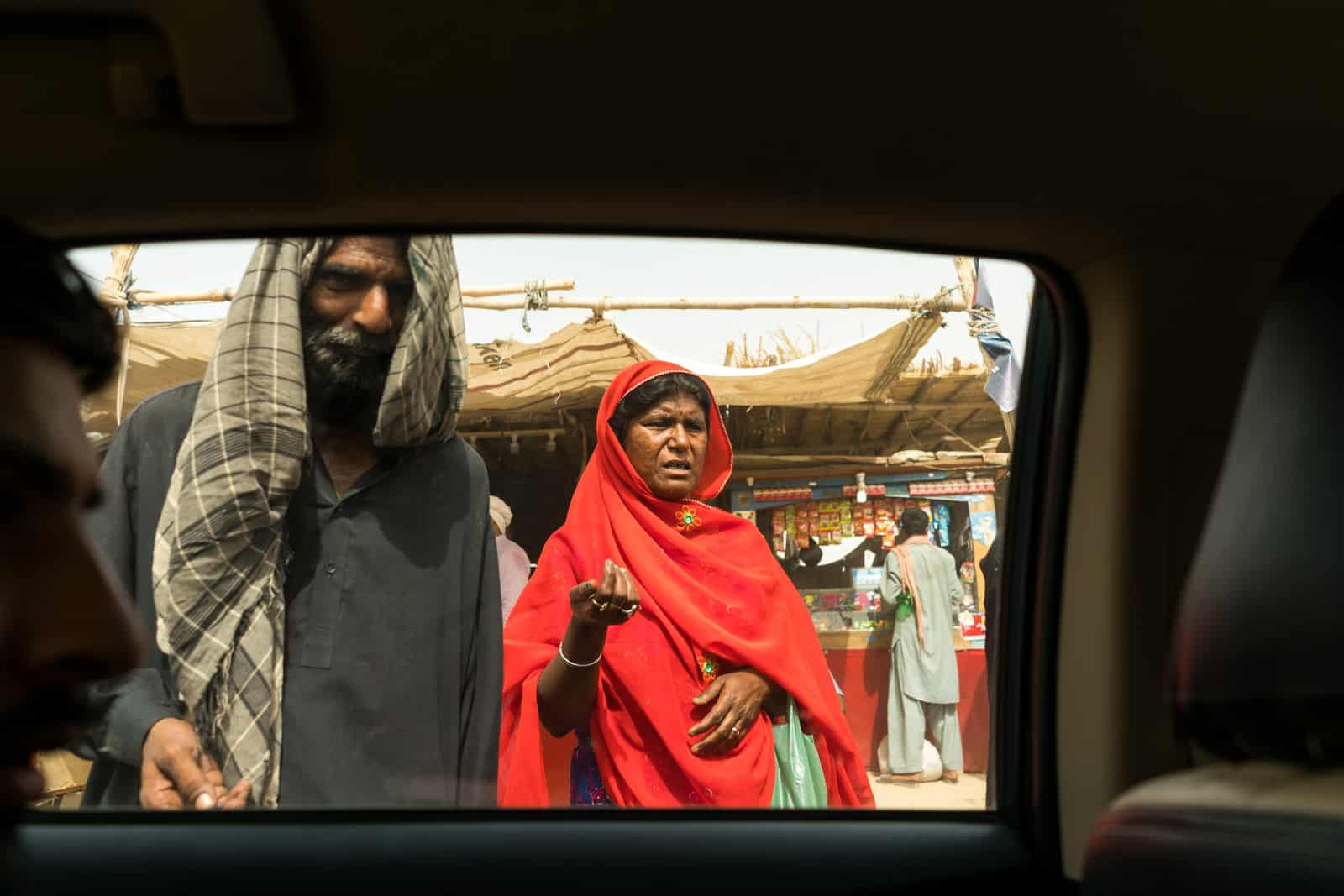 The Urs of Lal Shahbaz Qalandar in Sehwan, Pakistan - Beggars outside a car window - Lost With Purpose travel blog