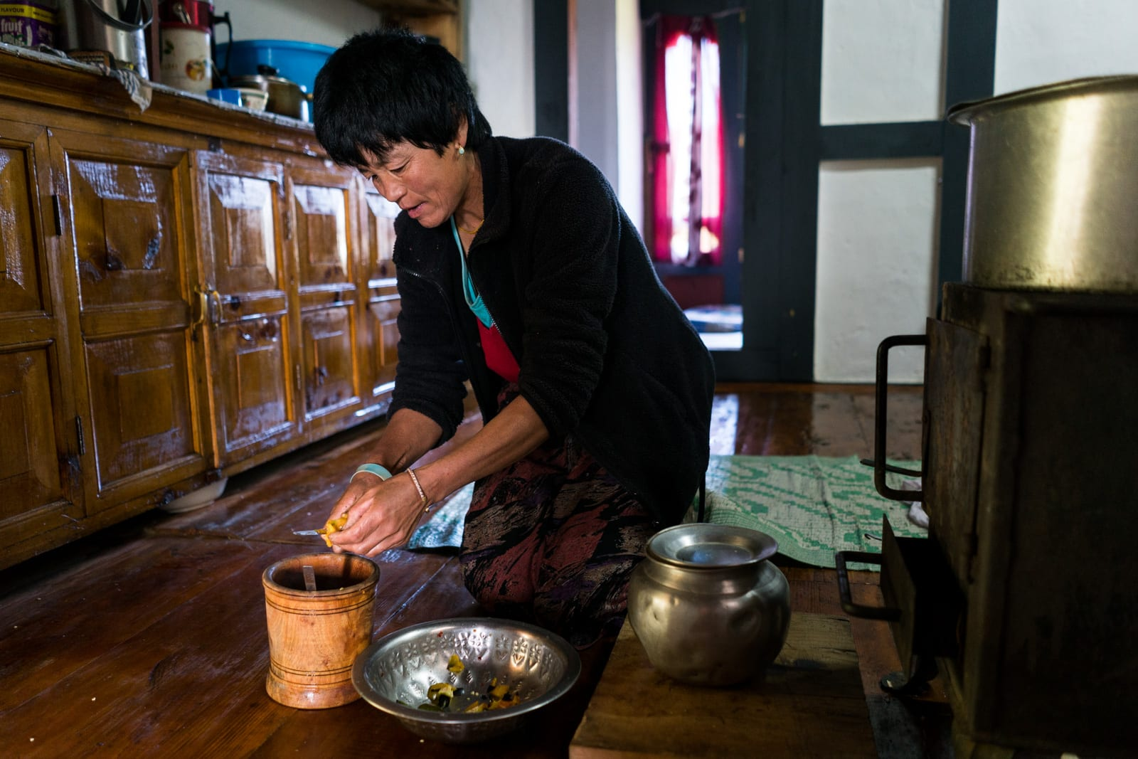 Photos of Bhutan - Homestay host in Phobjikha Valley cutting up chilies - Lost With Purpose travel blog