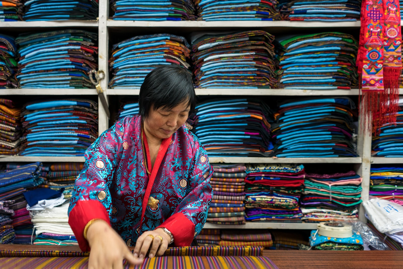 Photos of Bhutan - Woman folding traditional fabric for gho in Thimphu - Lost With Purpose travel blog