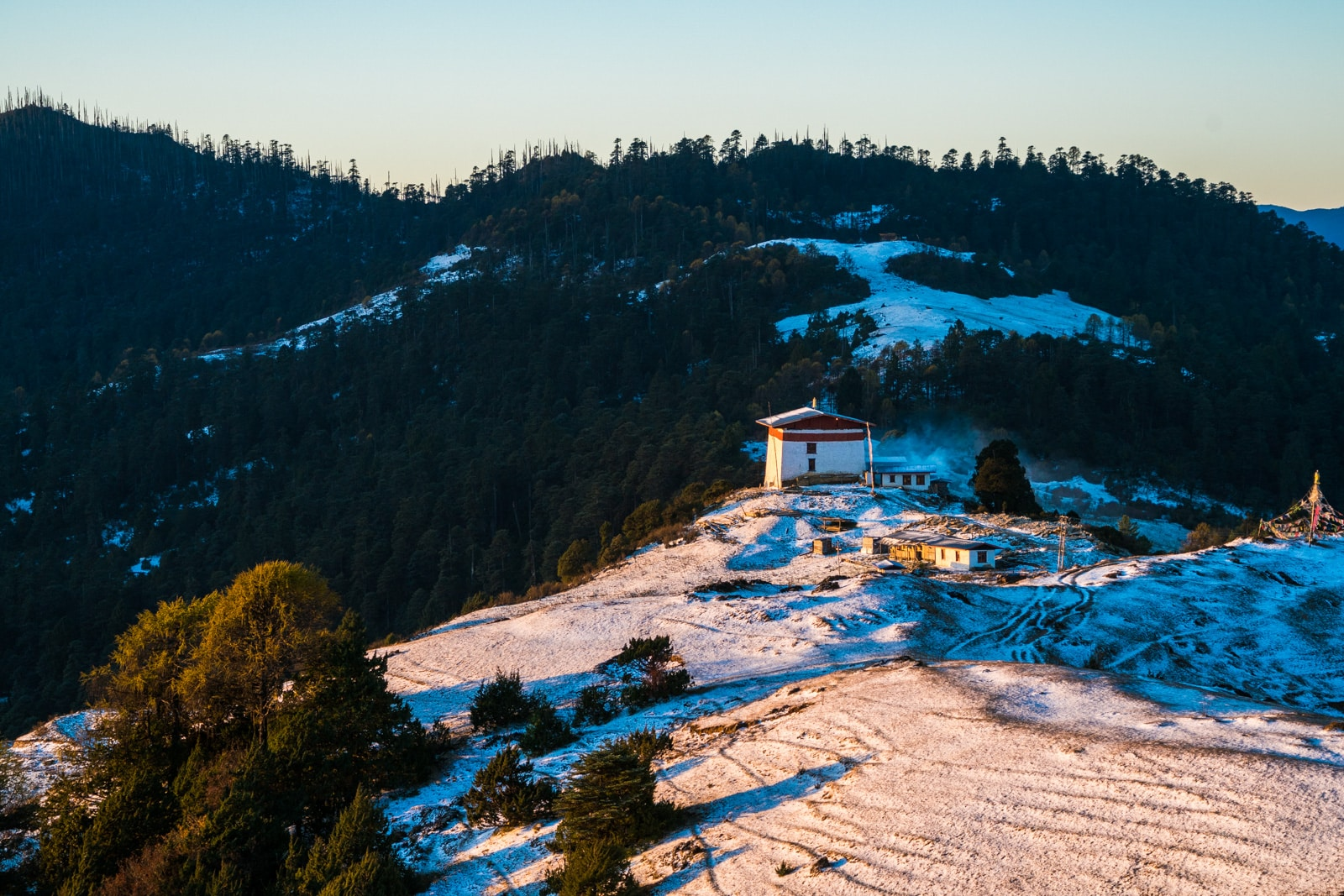 Photos of Bhutan - White snow at sunrise over Jele Dzong on the Druk Path - Lost With Purpose travel blog