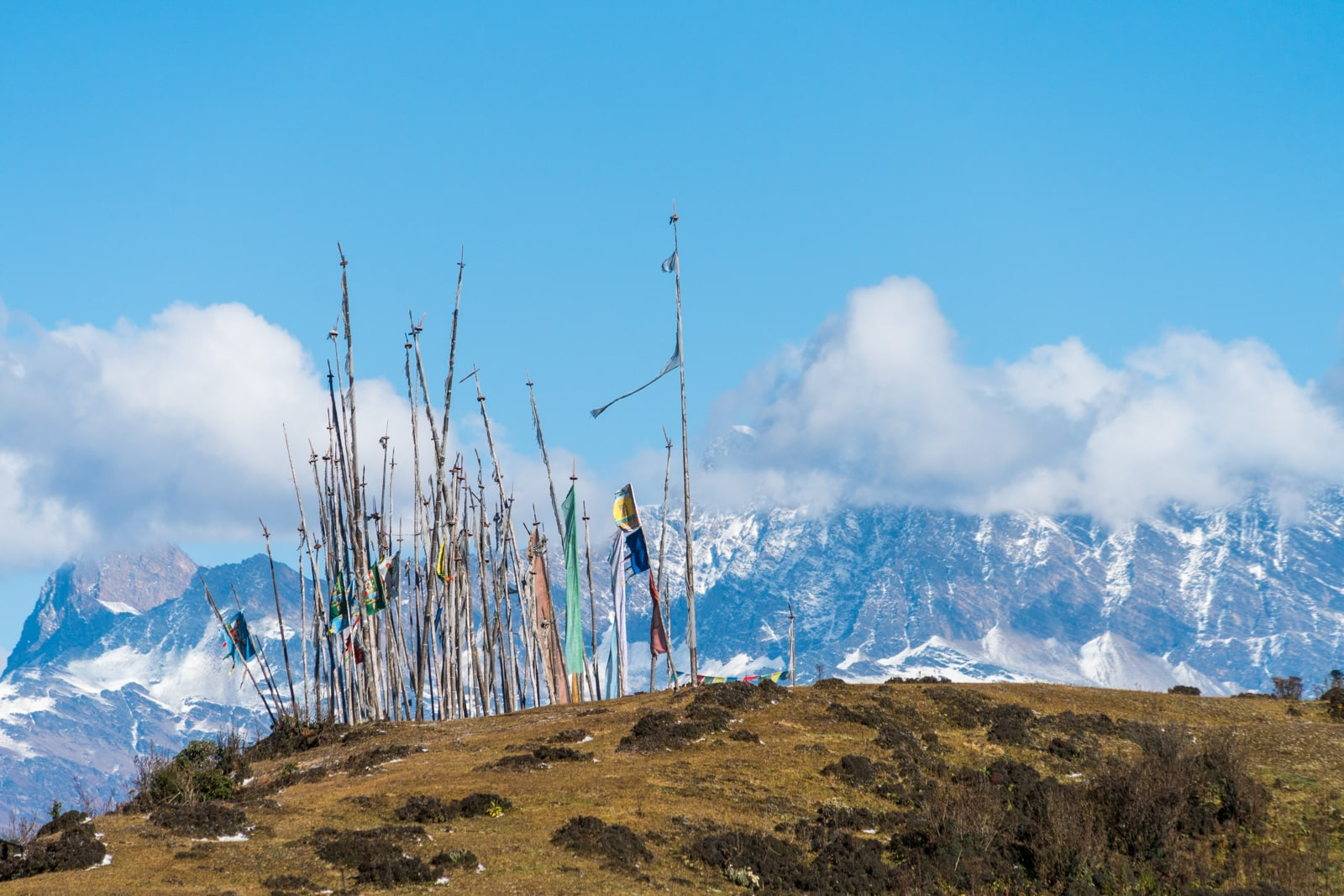 Photos of Bhutan - Prayer flags in front of snowy mountains on the Druk Path - Lost With Purpose travel blog
