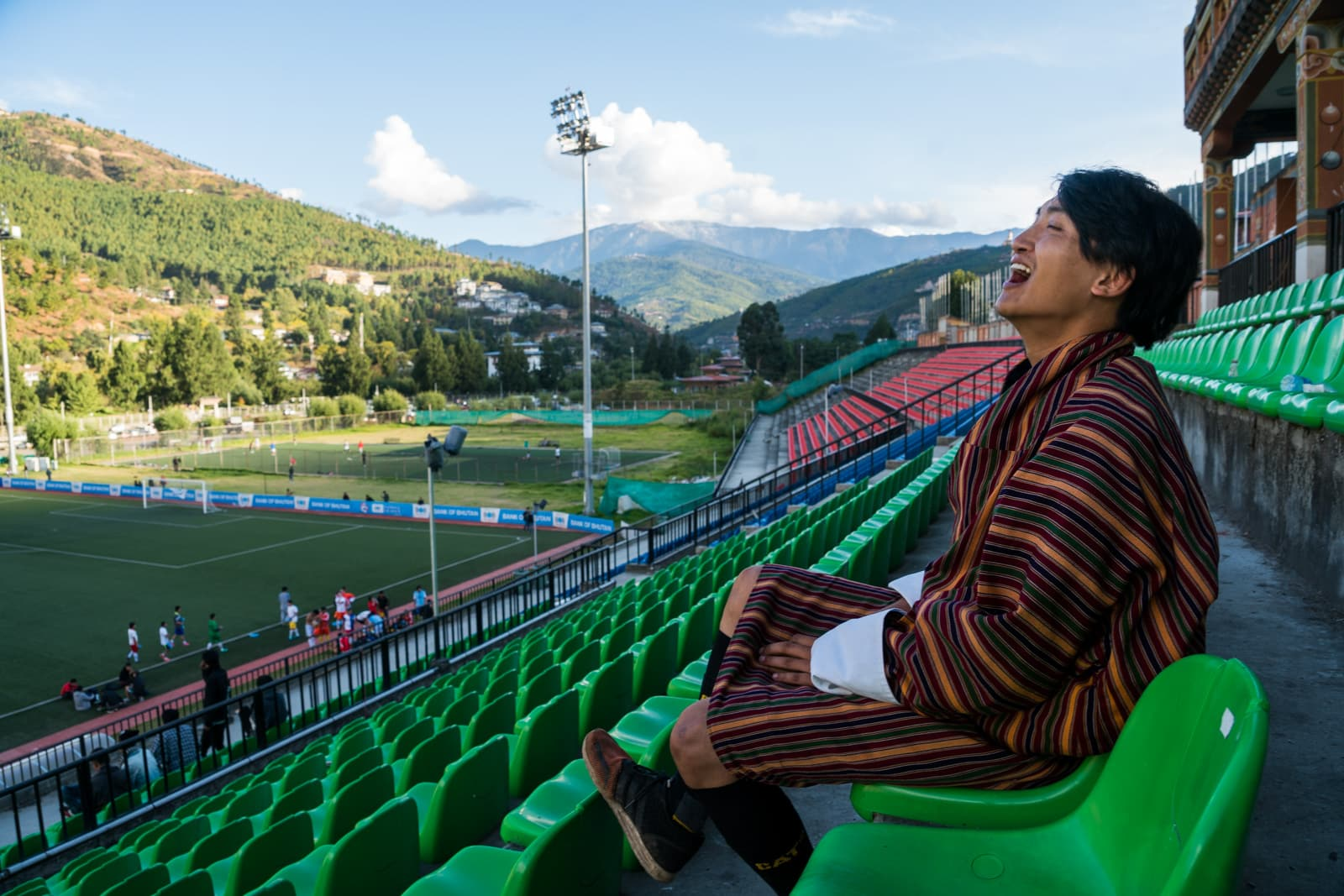 Photos of Bhutan - Tour guide Karma laughing in a football stadium in Thimphu - Lost With Purpose travel blog