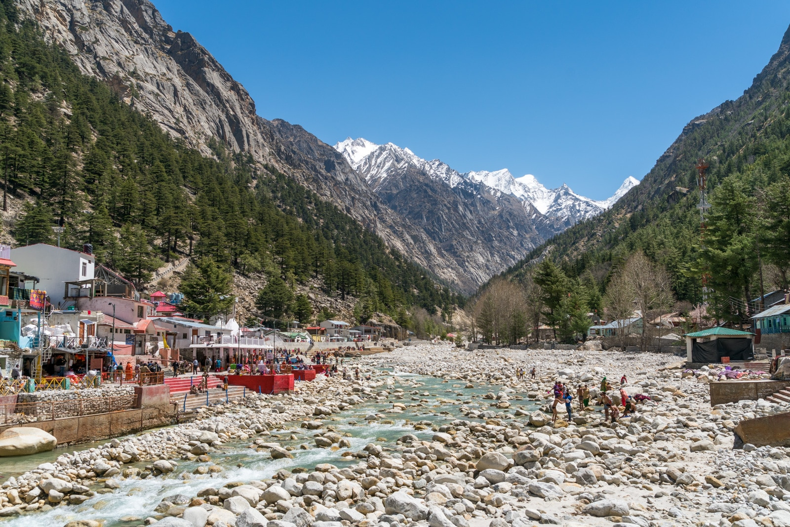 Guide to trekking to the start of the Ganges River in Uttarakhand, India - Bhagirathi River flowing through Gangotri town with pilgrims washing in the water - Lost With Purpose travel blog