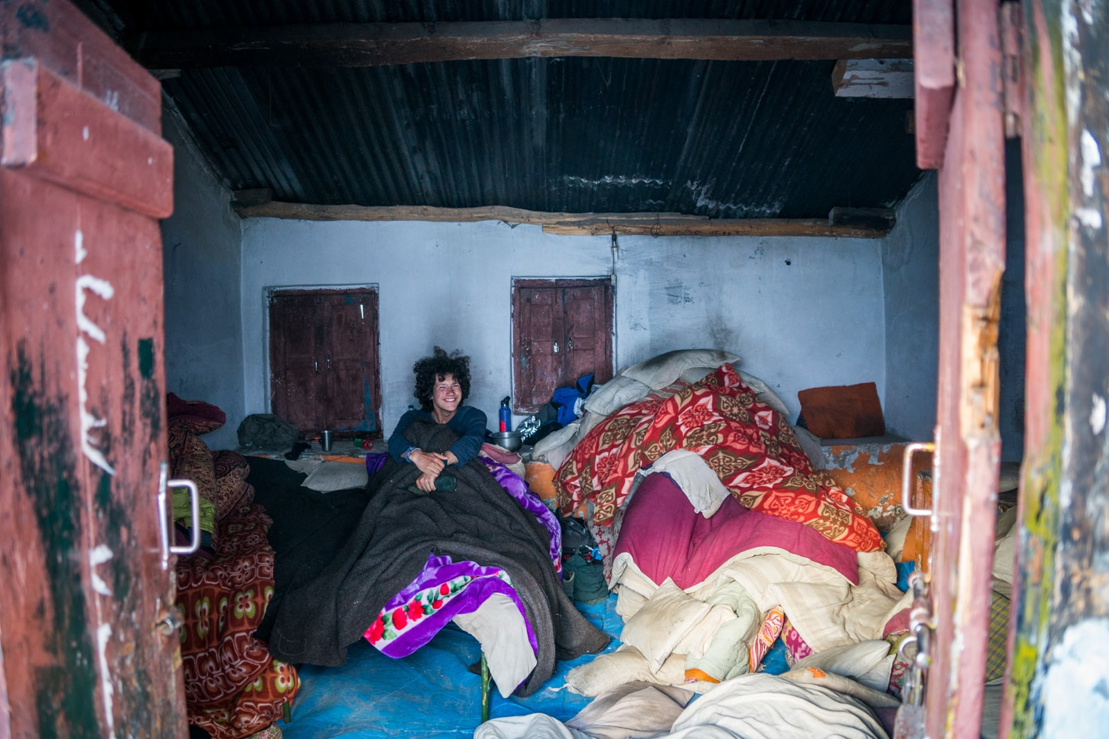 Guide to trekking to the start of the Ganges River in Uttarakhand, India - Boy in bed at Lal Baba Ashram in Bhojwasa - Lost With Purpose travel blog