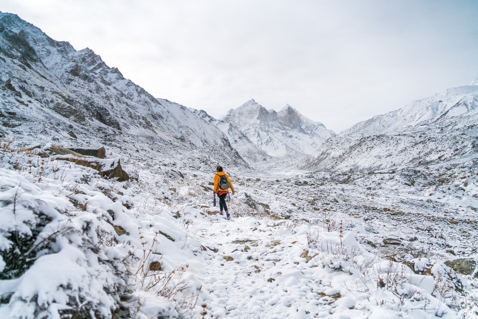 Guide to trekking to the start of the River Ganga in Uttarakhand, India - Walking in a yellow coat through snowy mountains - Lost With Purpose travel blog