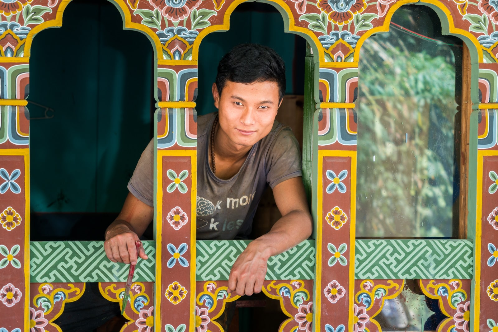 Stunning photos of Bhutan - Boy standing in a traditionally painted Bhutanese window - Lost With Purpose travel blog