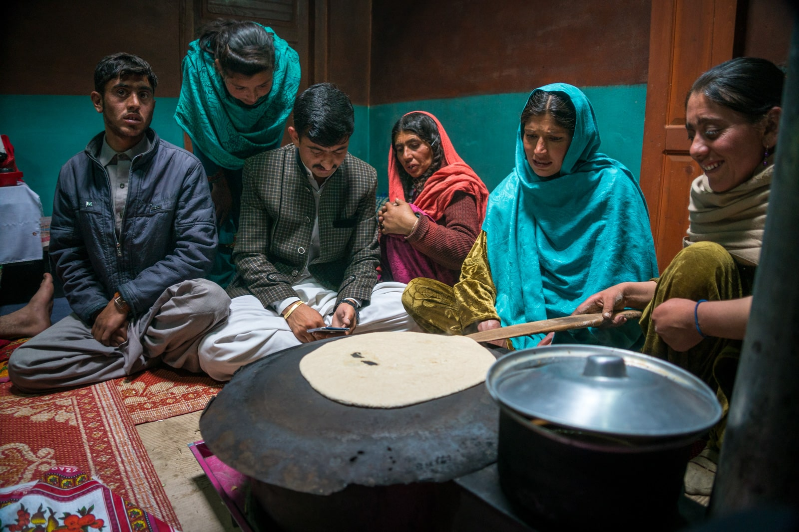 Phander Valley travel guide - Family in a traditional house with bread cooking on the stove - Lost With Purpose travel blog