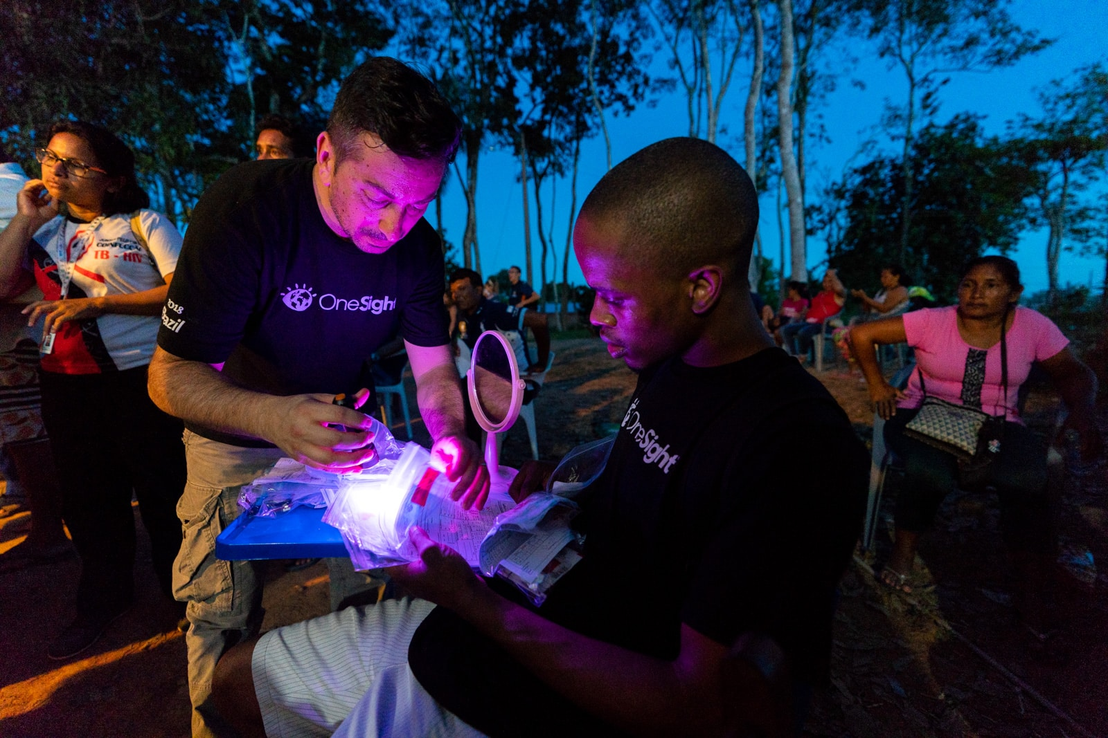 OneSight's mobile eye care clinic in the Brazilian Amazon - Volunteers sorting through glasses in the evening - Lost With Purpose travel blog