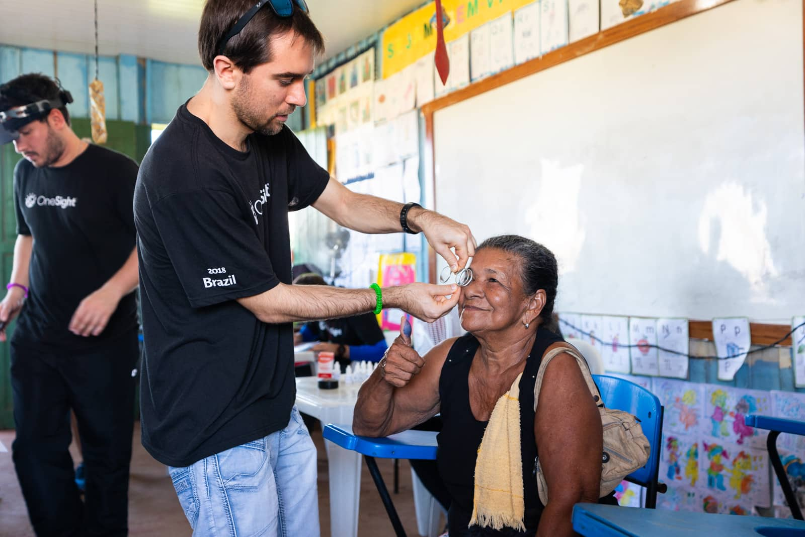 OneSight's mobile eye care clinic in the Brazilian Amazon - Australian volunteer Tom doing a check up on a patient - Lost With Purpose travel blog