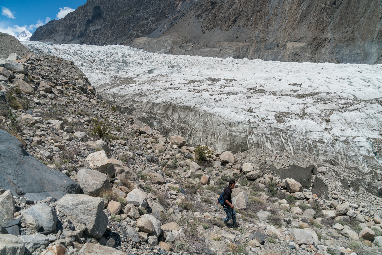 Homestay in Pakistan - Rehman looking for a path through loose rocks by Passu Glacier - Lost With Purpose travel blog