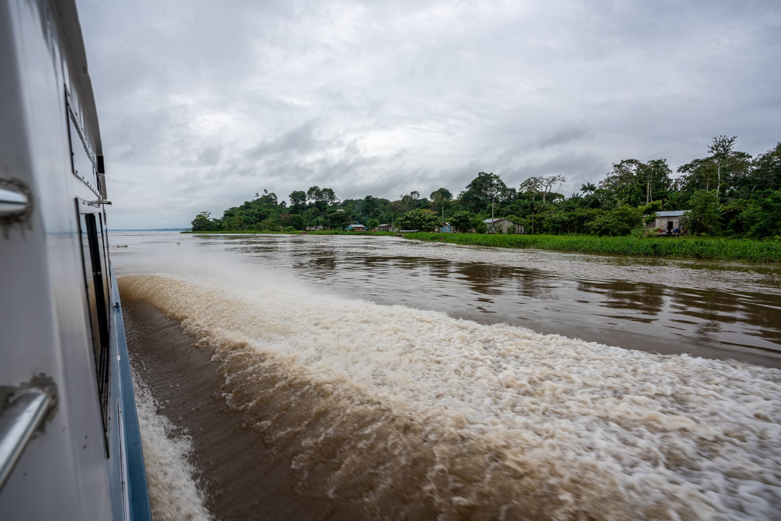 Taking the fast boat from Manaus, Brazil to Leticia, Colombia - Exterior of the fast boat and views of riverside Amazonian houses - Lost With Purpose travel blog