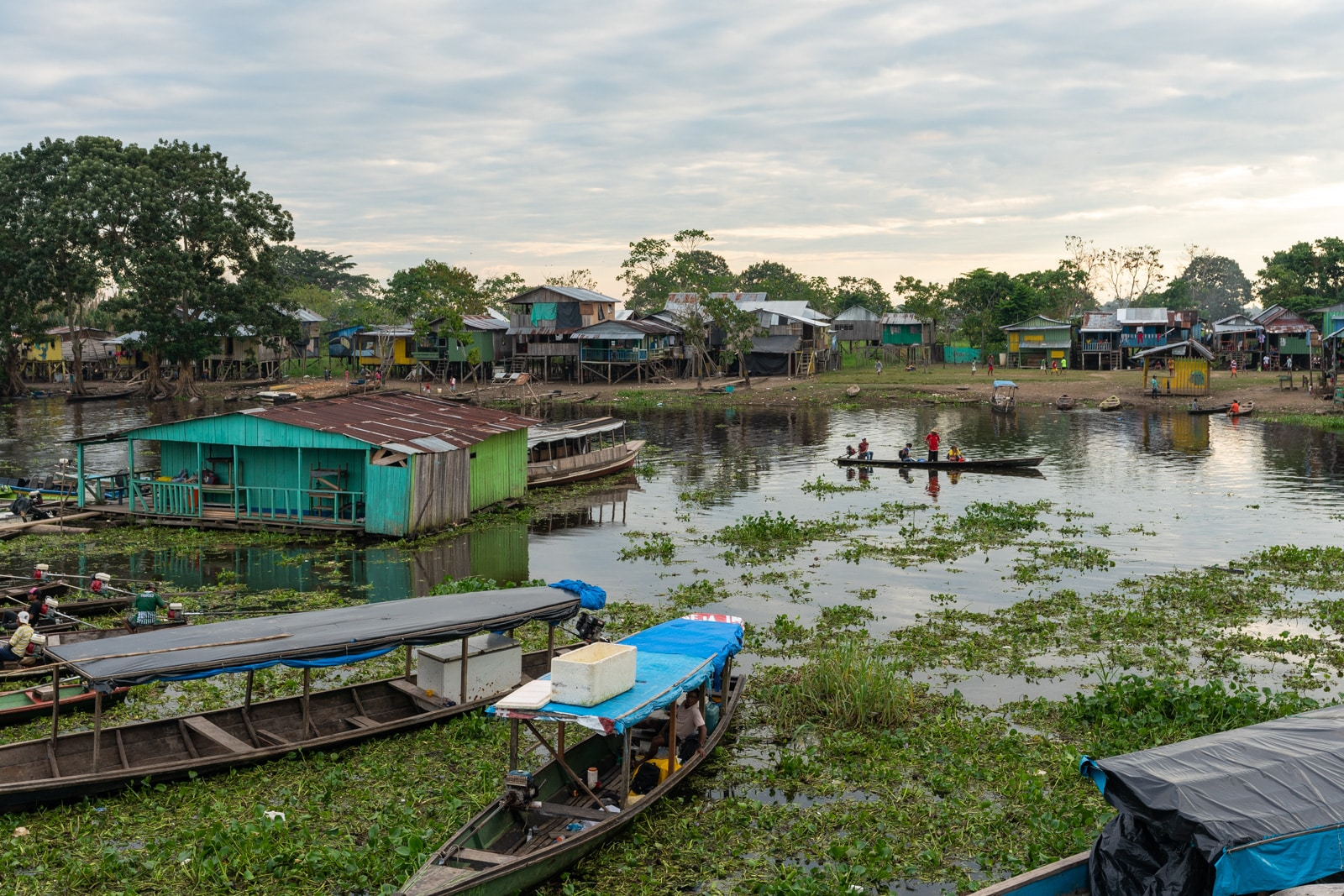 Taking the fast boat from Manaus, Brazil to Leticia, Colombia - Leticia canal at sunset with houses and people - Lost With Purpose travel blog