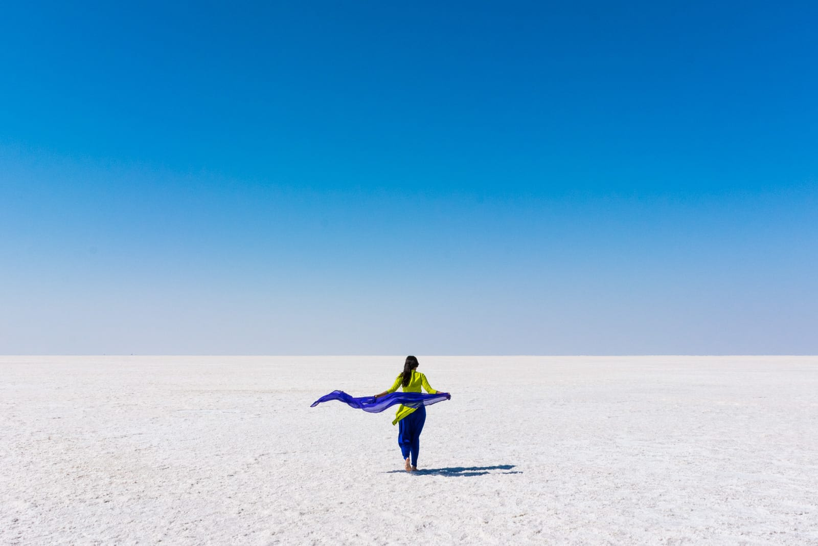 Reverse culture shock from long-term travel - Alex walking in the white desert known as the Great Rann of Kutch in Gujarat, India - Lost With Purpose travel blog