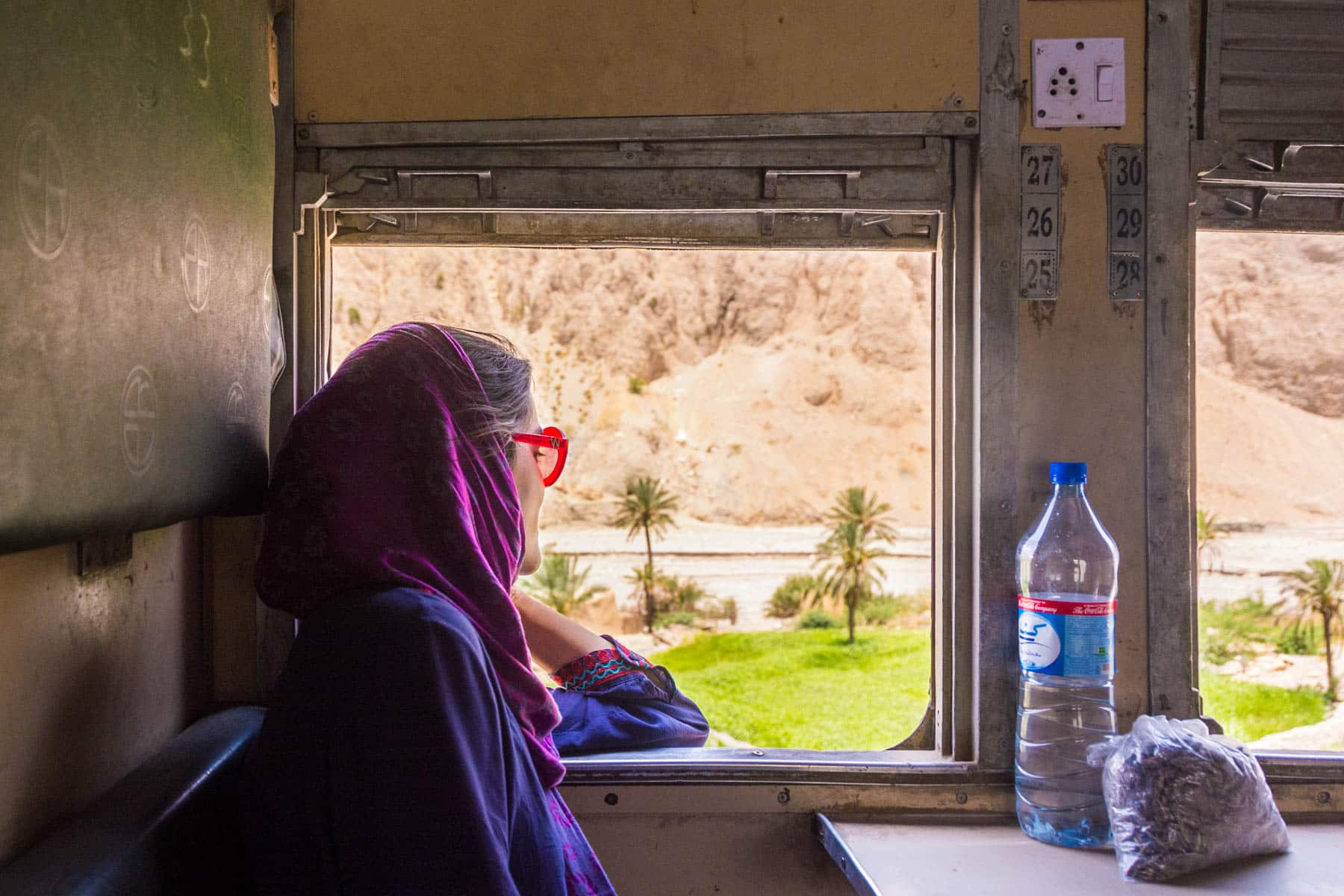 Reverse culture shock from long-term travel - Staring out the window on a train through Balochistan, Pakistan - Lost With Purpose travel blog