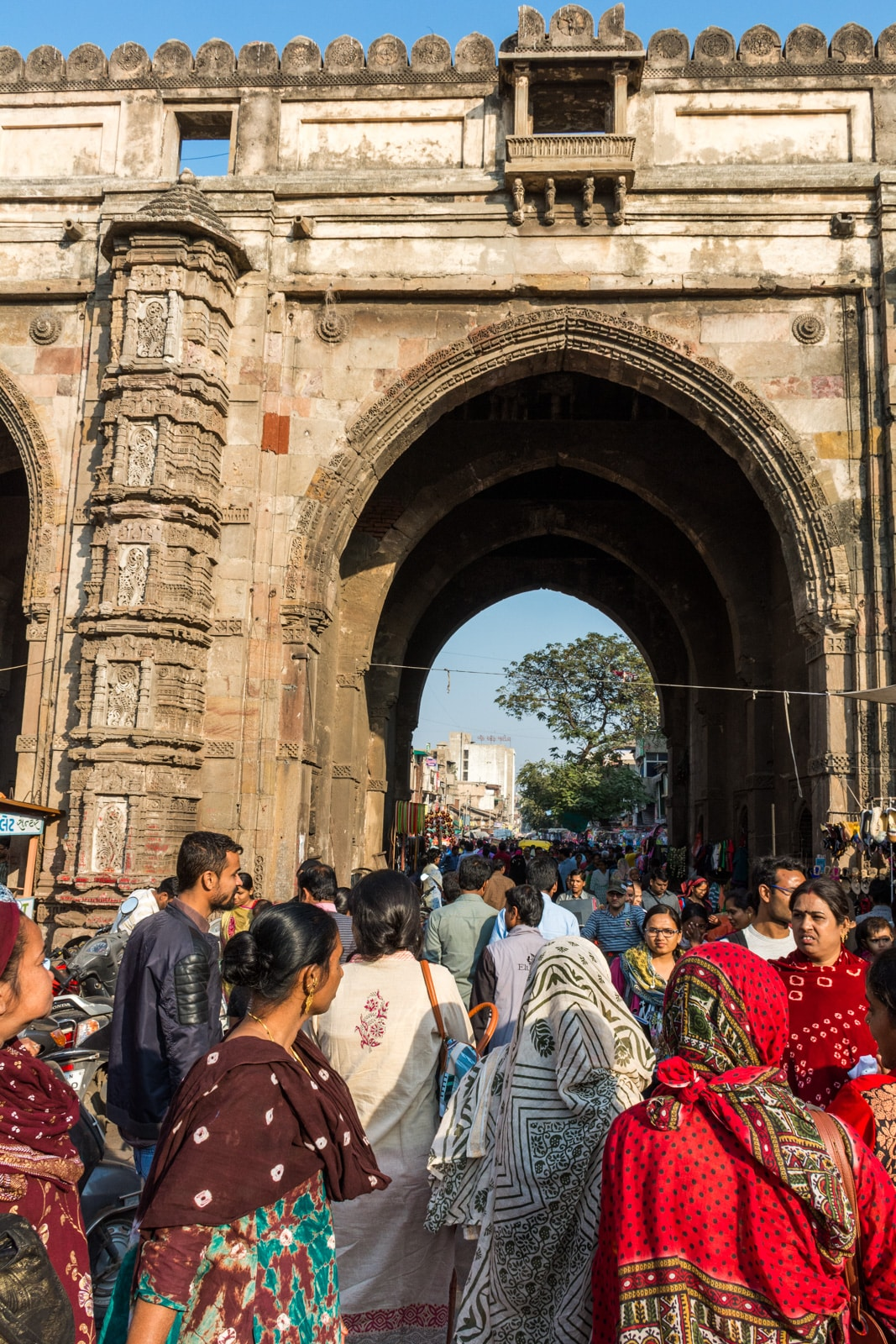 A busy crowd walks through an ornate stone archway over a market street in Ahmedabad