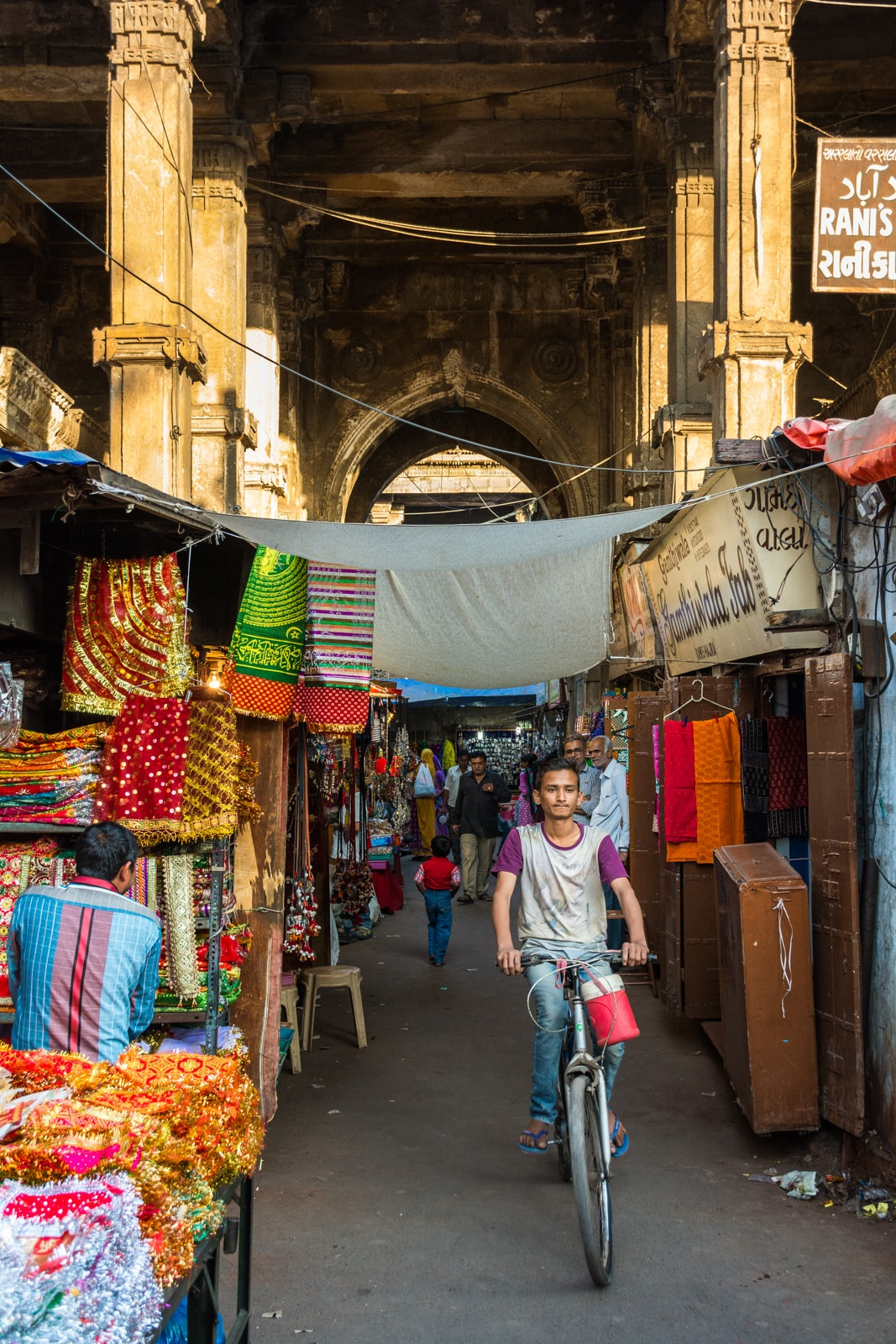 A young Indian boy riding a bicycle through a market street in Ahmedabad