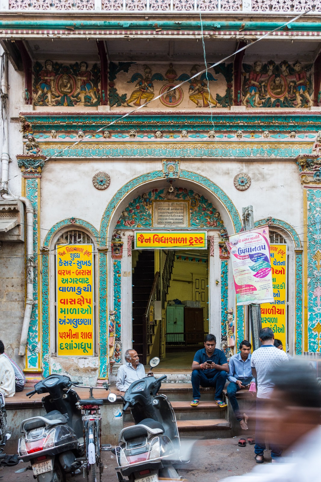 Men sitting outside a colorful traditional building in Ahmedabad, Gujarat state, India.