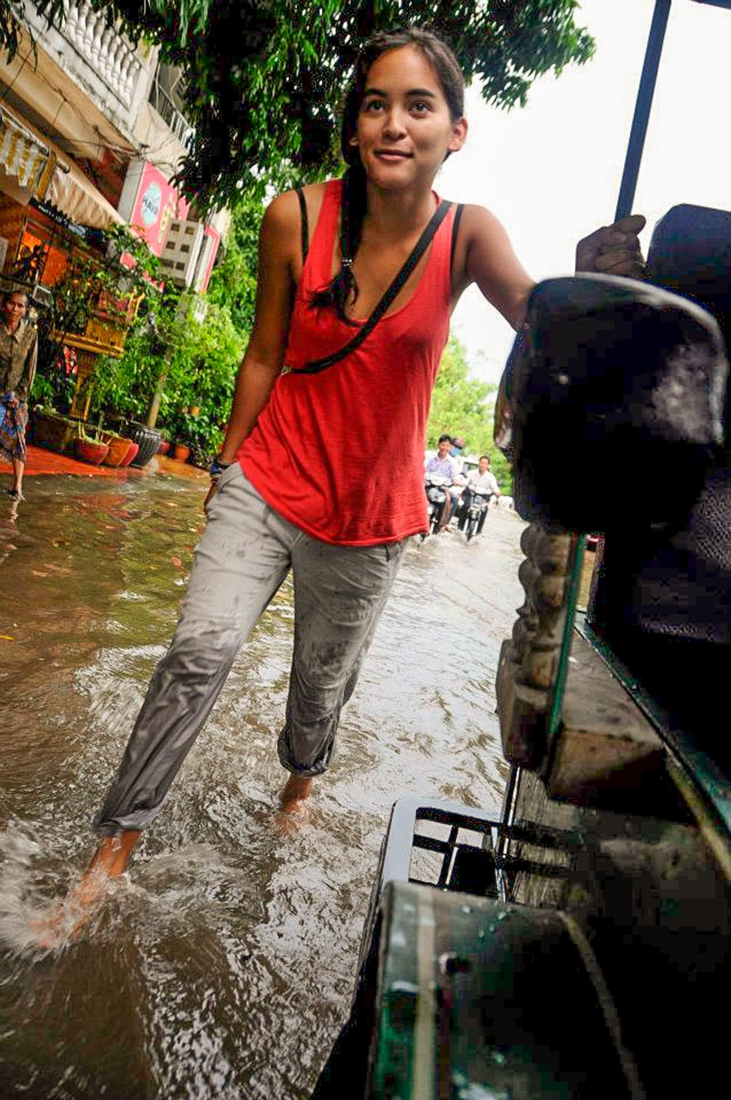 How I afford full-time travel - Pushing a tuktuk through Phom Penh, Cambodia during monsoon - Lost With Purpose travel blog