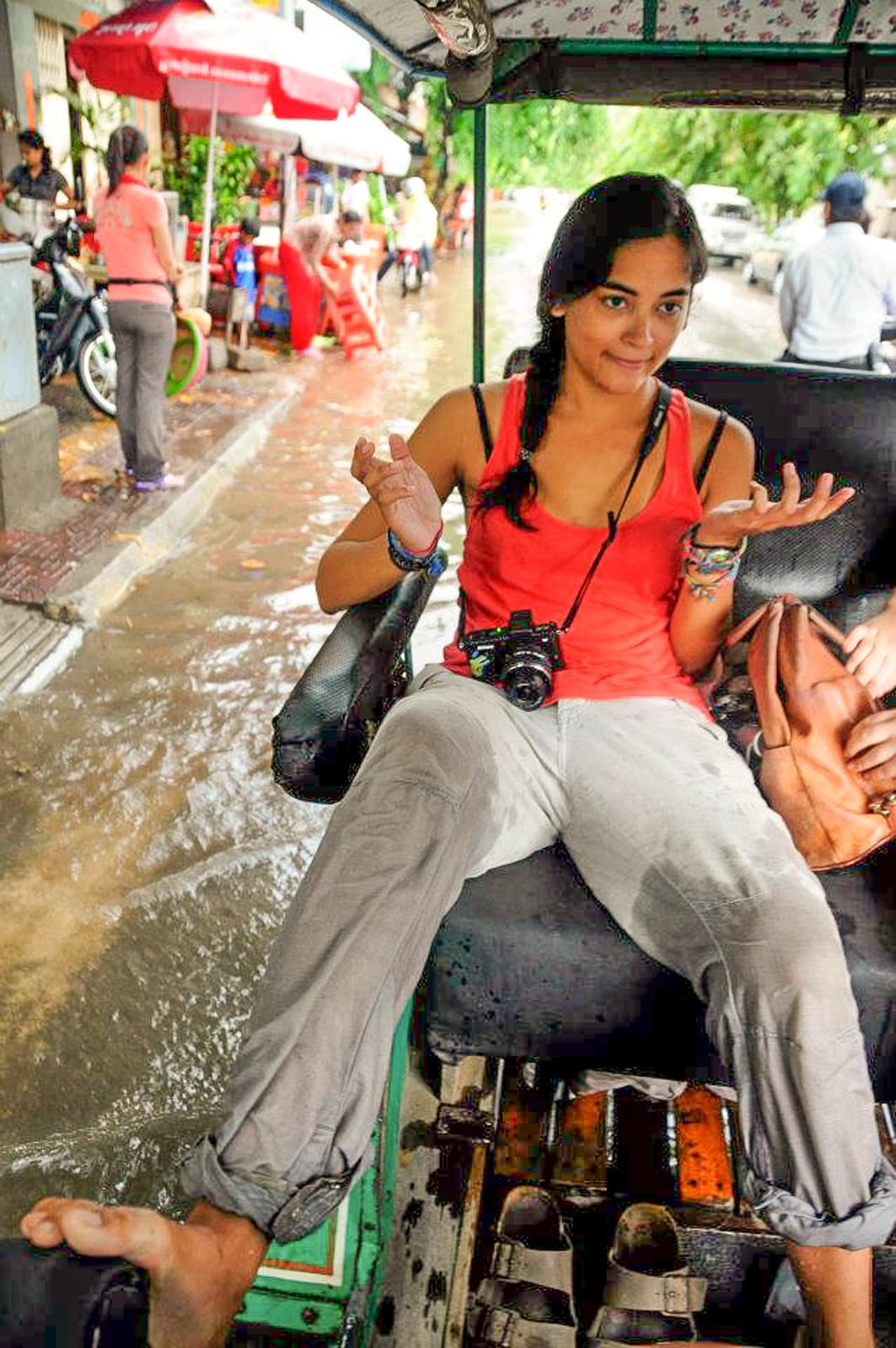 Female traveler riding in a tuktuk during a flood in Cambodia