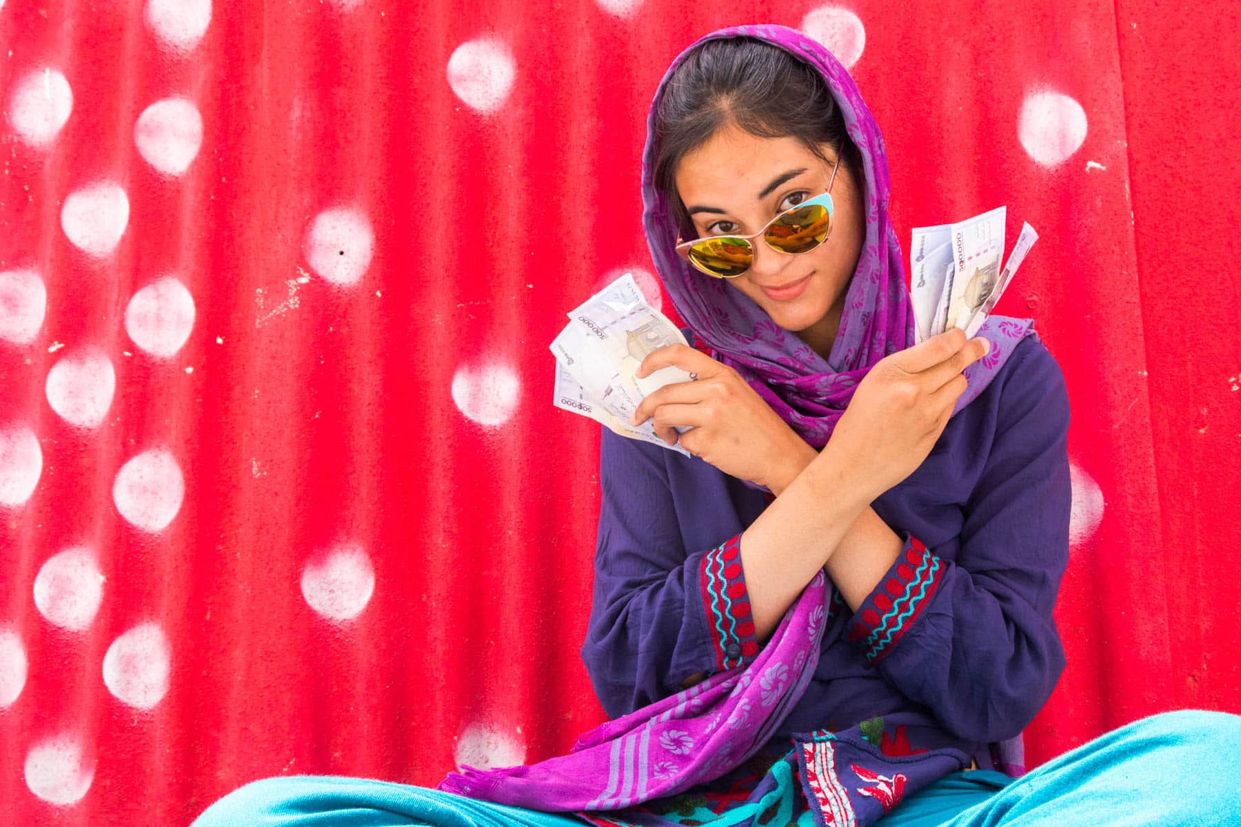 How I afford full-time travel - Alex holding wads of Iranian rials - Lost With Purpose travel blog