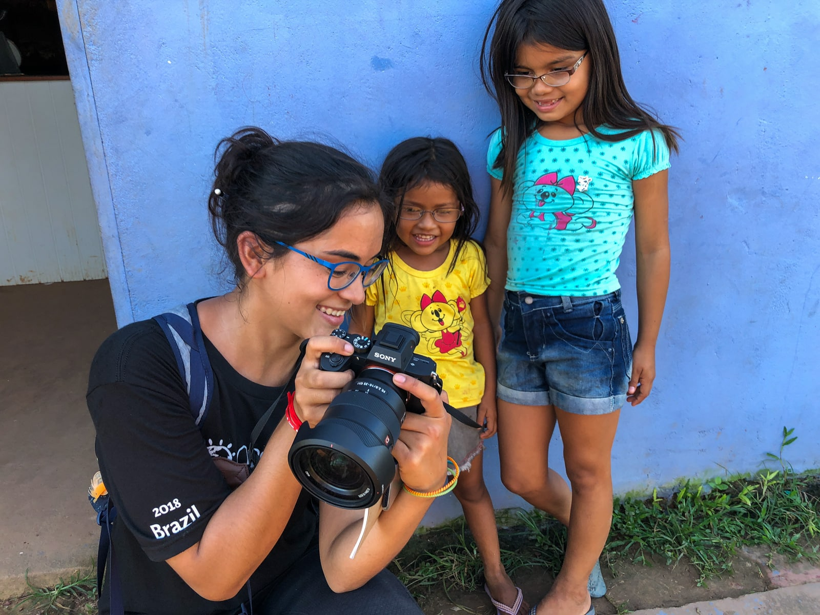How I afford full-time travel - Showing photos to two girls in Murutinga village, Brazil on the OneSight eye clinic - Lost With Purpose travel blog
