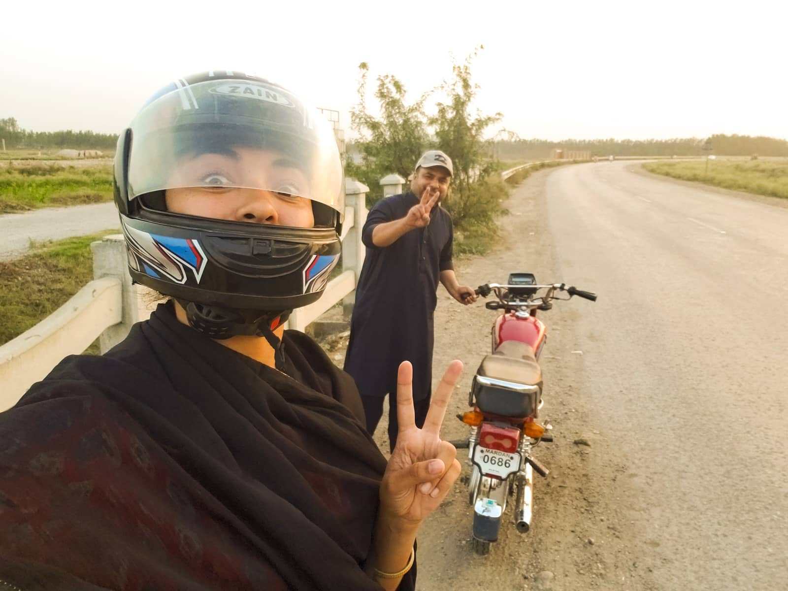 Motorbiking as a woman in Pakistan - Selfie with man and motorbike in Khyber Pakhtunkhwa - Lost With Purpose travel blog