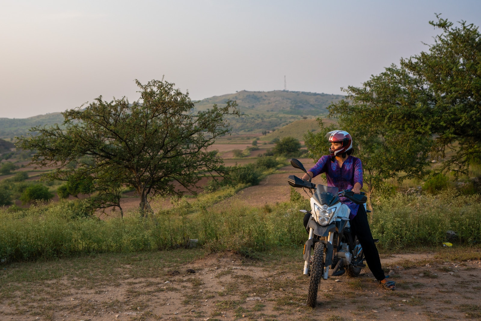 Learning to motorbike as a woman in Pakistan - Alex on a motorbike during sunset in Punjab - Lost With Purpose travel blog