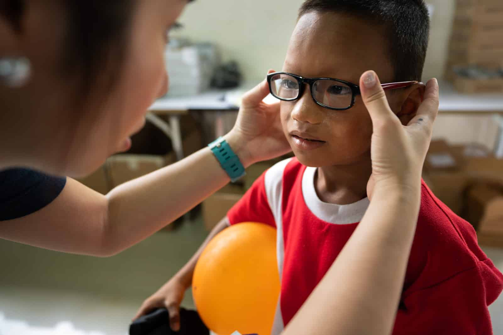 OneSight eye care clinic on the Thailand-Myanmar border - Young boy getting his glasses fitted at Mae Tao Clinic - Lost With Purpose travel blog