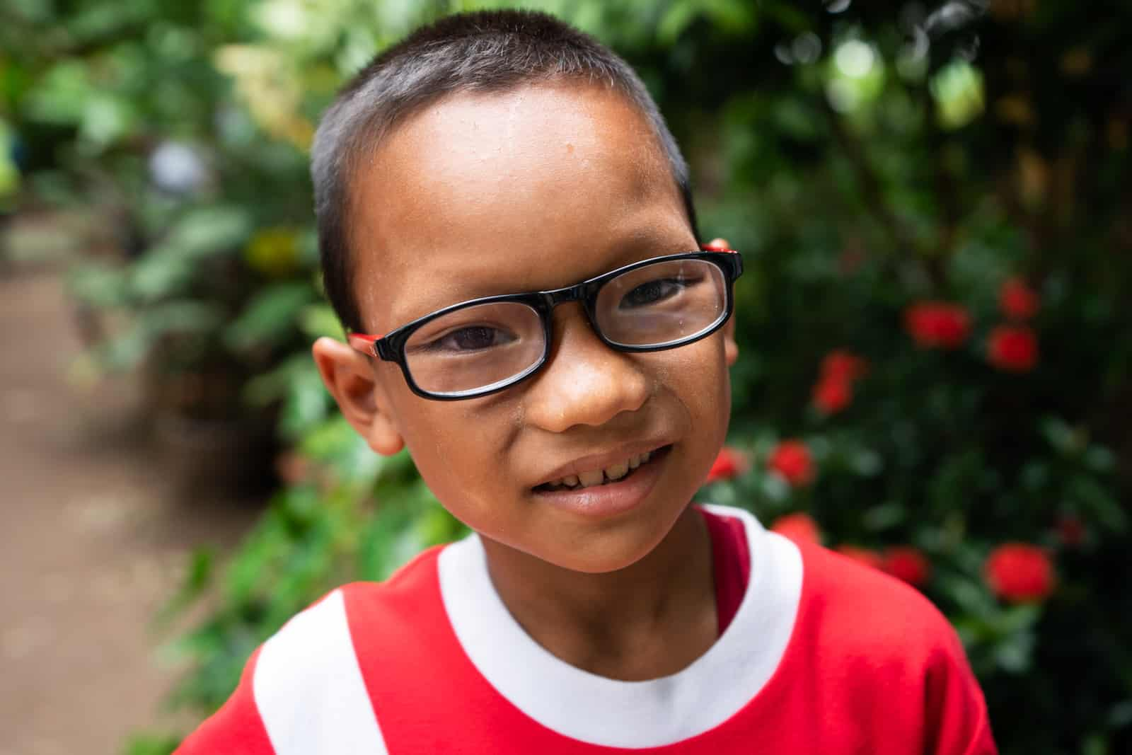 Eye clinic on the Thailand-Myanmar border - Young boy with glasses at the Mae Tao Clinic - Lost With Purpose travel blog