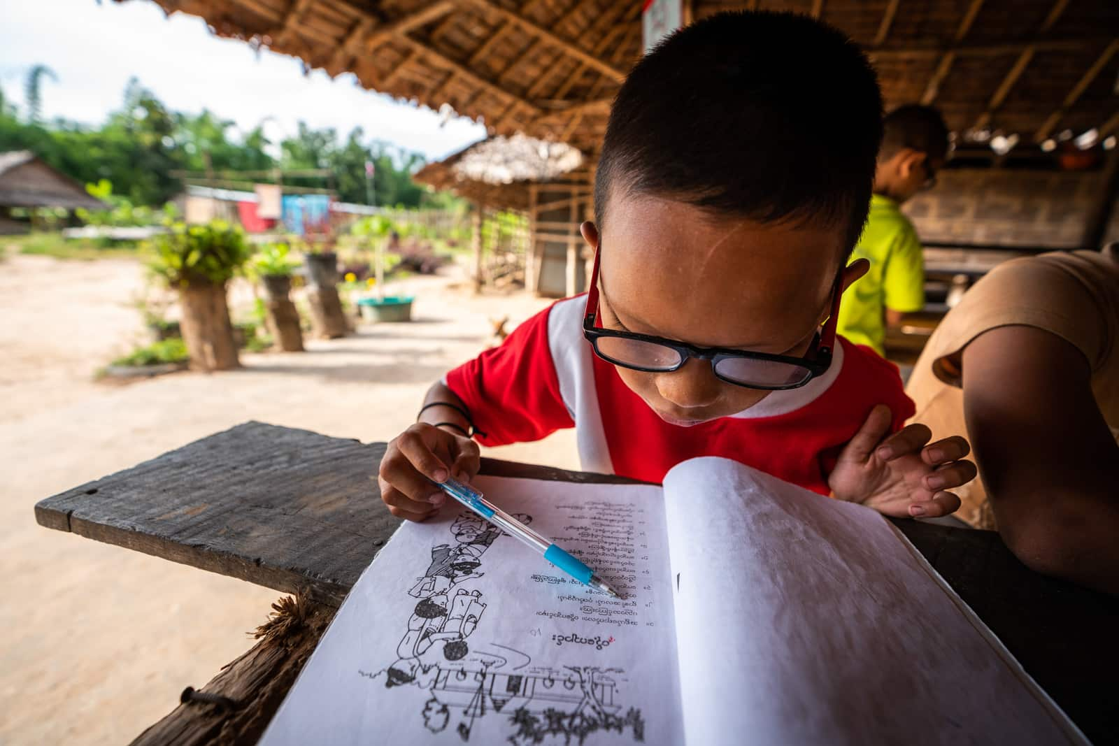 OneSight eye care clinic on the Thailand-Myanmar border - Sei studying a school book - Lost With Purpose travel blog