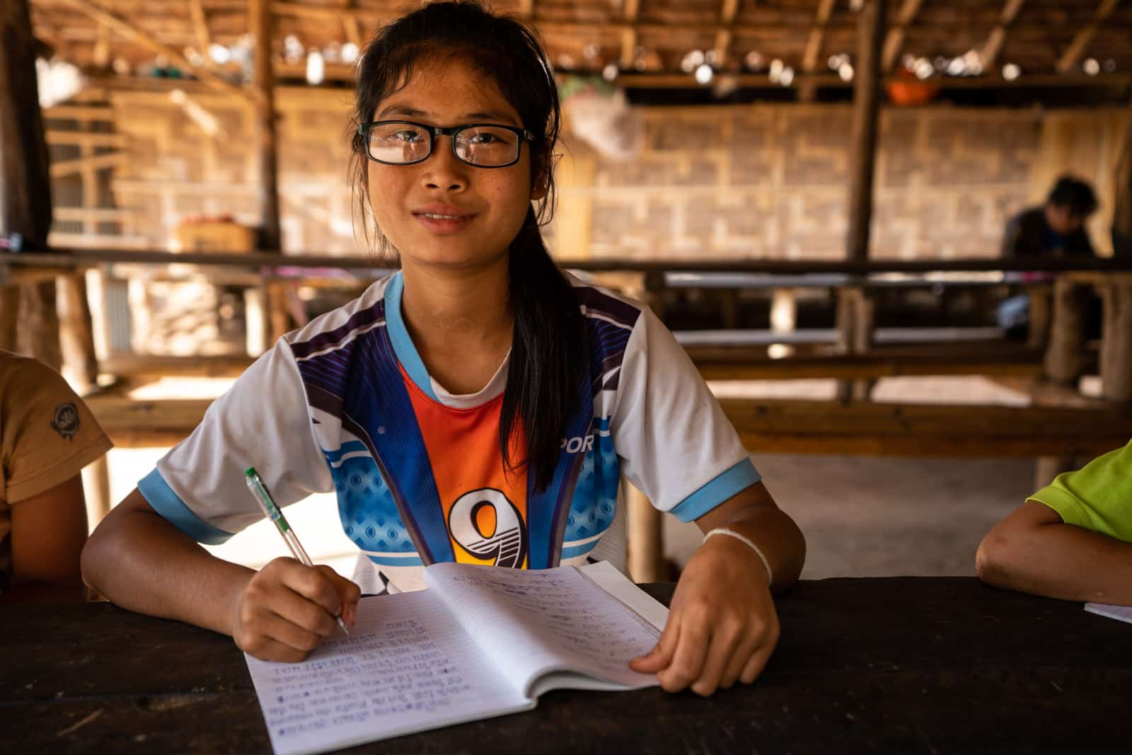OneSight eye care clinic on the Thailand-Myanmar border - Student with a workbook and glasses - Lost With Purpose travel blog