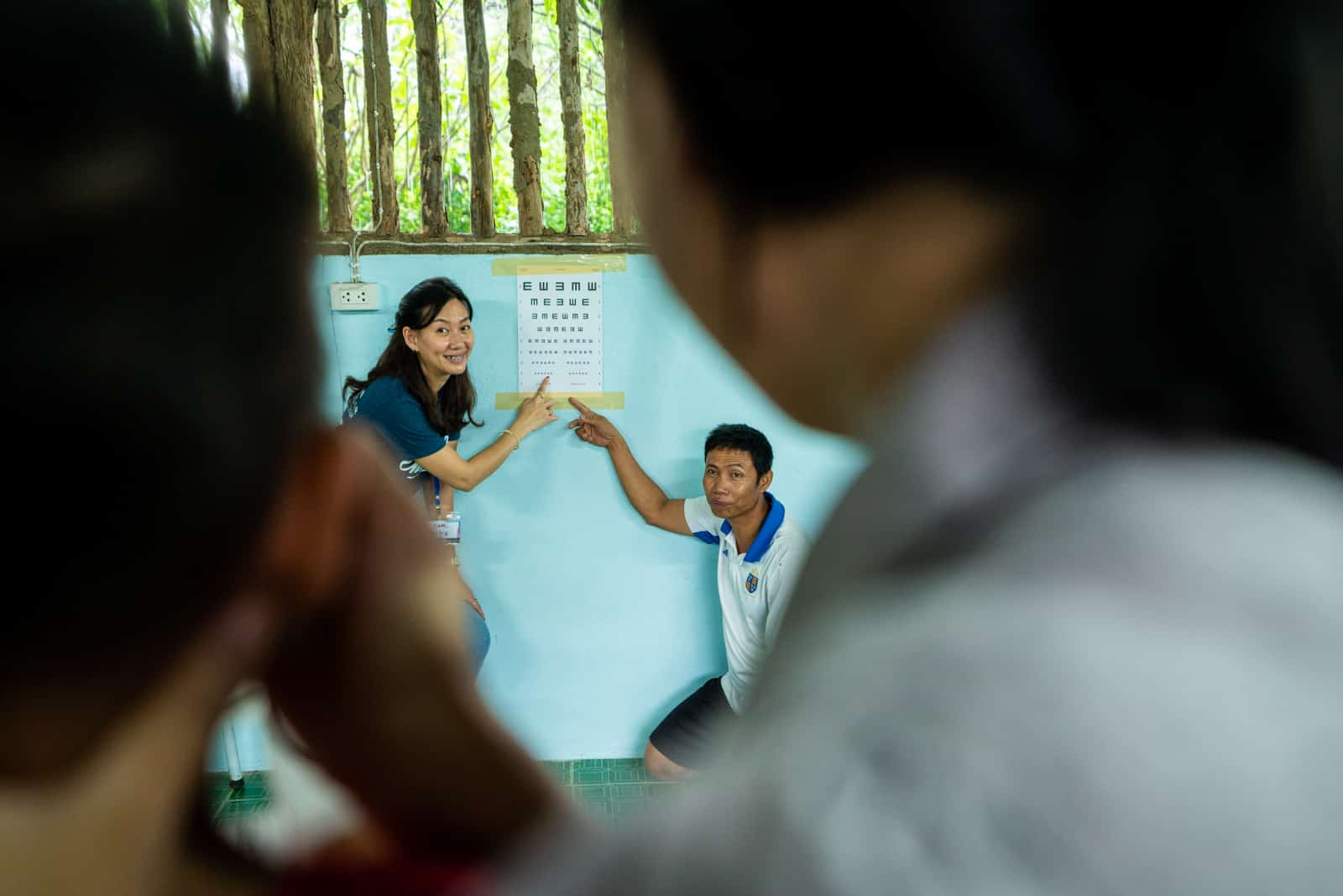 OneSight eye care clinic on the Thailand-Myanmar border - Volunteer and teacher doing an eye exam at a migrant learning center - Lost With Purpose travel blog