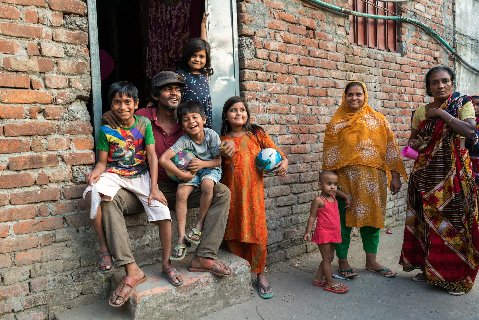 Reflections - Family sitting outside their home on the outskirts of Dhaka, Bangladesh - Lost With Purpose travel blog